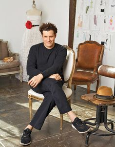 fashion designer isaac mizrahi in his design studio with leather chairs and dress. NOTE THE FASHION SKECTHES!!!! Great Idea.