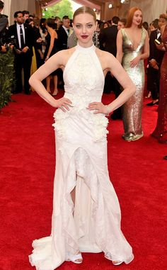 2015 Met Gala: Amanda Seyfried is wearing a white sleeveless Givenchy gown with a high low hemline. White is angelic and fierce on Amanda! I like the bold red lip as a fun pop of color!