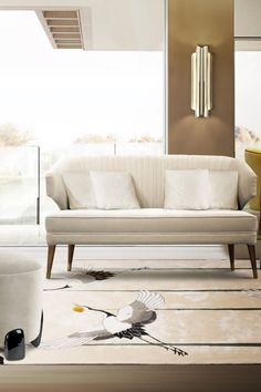 This modern living room interior is filled with upholstery, from the IBIS 2 Seat Sofa to the NOAKI Stool and the IBIS Armchair, and these luxurious velvet items are evidenced by the CYRUS Double I Wall Light and the BRYCE Side Table.  #livingroomdesign #contemporarylivingrooms #modernlivingrooms #classiclivingrooms #mid-centurylivingrooms #eclecticlivingrooms