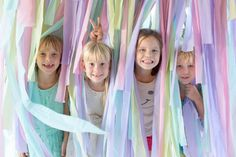 A gaggle of party-goers stand amid a playful streamer photo backdrop, made from plastic tablecloths.