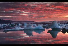 Red & Blue SUNSET - Jökulsárlón, Iceland;  with reflections from the icebergs;  the photographer stated this was taken in July (2011) and SUNRISE was TWO hours later!;  photo by orvaratli, via Flickr