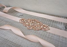 This delicate rose gold sash is truly stunning and would add the perfect finishing touch to your wedding dress. Vintage inspired, and studded with hundreds of high quality rose gold / peach rhinestone crystals and pearls held in silver claws, this belt glitters, gleams and catches the light making it a real show stopper. The rhinestones are securely attached to double sided pale peach satin ribbon for a really high quality feel. You can choose your own ribbon colour for your sash from…