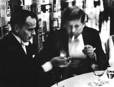 Frank Sinatra lights John F. Kennedy's cigar at a private dinner during the 1961 Inaugural festivities.