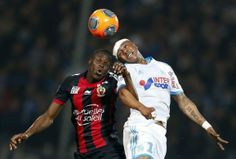 Olympique Marseille's Andre Ayew (R) jumps to head the ball with Nice's Romain Genevois during their French Ligue 1 soccer match at the Velodrome stadium in Marseille, March 7, 2014. REUTERS/Jean-Paul Pelissier...