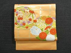 This is a glamorous Nagoya obi with a design of seasonal flowers circle on lattice, which is woven with gold foiled threads