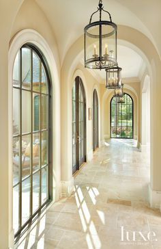 Hallway with hanging light pendants   LuxeSource   Luxe Magazine - The Luxury Home Redefined.  Airy light pendants from Currey & Company's Lillian August collection, purchased at Hinsdale Lighting, hang in a neat row in the home's main gallery.