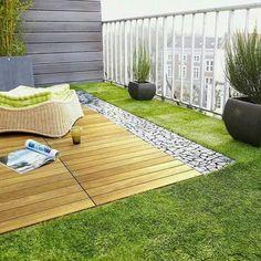 Combinación de césped, madera y piedras en una terraza.