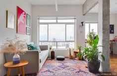Apê compacto tem vigas e colunas de concreto aparente, tapete étnico e sofá cinza.