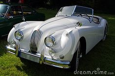 Beautiful white, classic antique Jaguar car with the top down.
