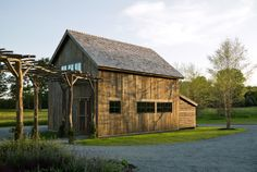 The siding is mushroom wood, and the roof is wooden shake. The main house and utility shed are joined by a black locust pergola, and the are...