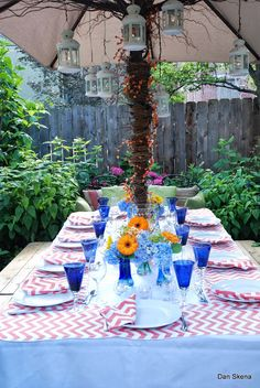 True-blue water glasses play off of the pink checkered picnic tablecloth for this backyard garden party.
