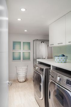 Better believe utilitarian spaces can be incredibly chic. Pale green accents are fresh companions to this laundry room's crisp white walls and cabinets. Even the stainless steel washer and dryer feel like a part of the decor.