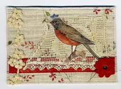 Measures appx 4 x 6 inches and is quilted with batting in the middle, a coordinating off white wool felt on the back.  linen fabric, a reprint on fabric of a red bird, some venise lace trim, a piece of repurposed  vintage lace and a leather flower.    See more of my fabric art and postcards at http://www.twocooltexans.etsy.com