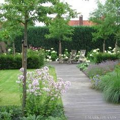 Terras van hout, mooie beplanting. Afwisseling gras en beplanting.