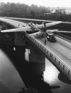 A B-17 is towed by a truck across the Mad River Bridge to the United States Air Force Museum at Wright-Patterson Air Force Base in Dayton, Ohio (1957)