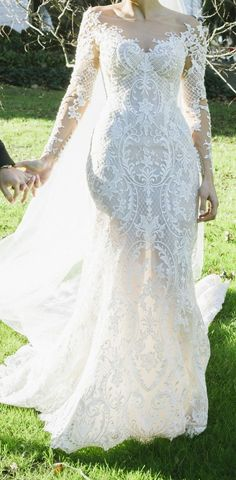 This sheer long sleeve #bridal gown has a pretty neckline. The embroidery continues all the way to the hem. Wedding #Dresses with unique embroidery from #Darius Customs are affordable. We are in the #USA and offer custom #weddingdresses that are reasonable in price. Making #replicas of #hautecouture #dresses is also an option. So if what you want is too much for your budget email us for help.