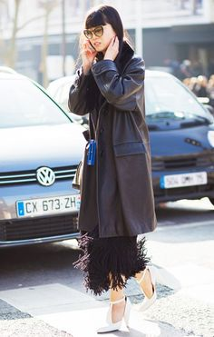 Leaf Greener wears a black fringe dress, leather trench coat, cat-eye sunglasses, and white t-strap pumps