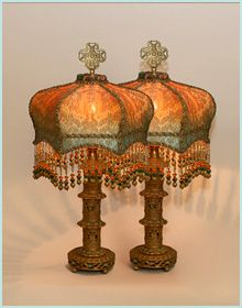 Pair of bohemian style antique table lamps hold a pair of hand-dyed Crown silk lampshades. The shades are ombre-dyed from deep amber into teal. The shade is covered with a beautiful Byzantine style golden bronze antique metallic lace. Colorful hand beaded fringe adorns the bottom of the shades.