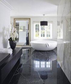 salle de bain en marbre noir et blanc revêtement sol baignoire autonome blanche design épuré tendance
