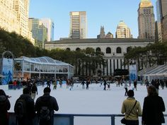Under clear blue skies, New York ice skaters enjoy the ice skating rink at Bryant Park in Midtown NYC!