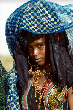 "Africa | a Wodaabe nomad bride believes that her birthright of beauty comes from her original ancestors Adam and Adama. The small talisman pendants worn around her neck are believed to protect her and maintain her beauty throughout married life. Niger, 1992. | ©Carol Beckwith & Angela Fisher. Publication ""African Ceremonies"""