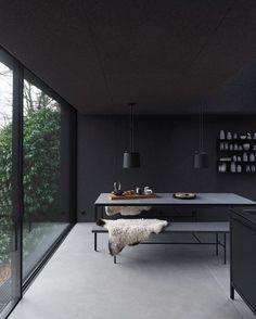 Black kitchen with polished concrete floor and full height black metal framed sliding door. Dream kitchen.