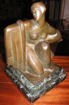 This is a lovely sculpture of a woman, made in Belgium in the 1930's, and cast in bronze with a green marble base. Although petite in size this statue has a great presence. Although the artist, Canneel, was classically trained his style gradually moved toward expressionism. He was known for doing sculptures on a larger scale, along with ornamentation on public buildings in Belgium.
