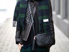 A Gucci camera bag is paired with a leather jacket, sweater, and plaid pieces