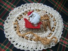 """What will children think when they see you wearing this brooch? It is a nice reminder to them that Santa is watching to see if they are naughty or nice. I crocheted the backing and a gold crocheted chain is fed through the eyelet and tied into a bow at the bottom. Next I starched the crochet back stiff and I sewed on the Santa, sleigh, and reindeer. A nickle pin back is hot glued to the crochet back. Looks great on clothing, scarves,Jackets, or to top a gift. Measures 4"""" x 3""""."""