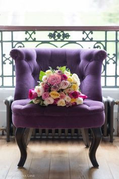 The beautiful bouquet of flowers on the velvet purple chair, against the green scroll iron work. Color | Design | Pattern | Inspiration