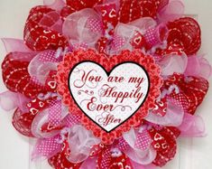 New, Large, Premium Valentines Day wreath. A large, Valentine heart rests on a bed of pure white deco mesh. The accent is black and is decorated with white, Happy Valentines Day lettering. Adorable white swirls and letter red hearts border the heart and a glittering red arrow pierces the center. The inner is decorated with black herringbone ribbons and gorgeous black and white stripe ribbons with glittering red hearts. The outer ring is made of bright red shimmering deco mesh with black, red…