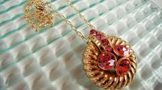 Sparkling vintage inspired pendant necklace is an assemblage of recycled jewelry and vintage buttons. Pink rhinestones add sparkle to the gold tone pendant and chain. Great accent for a wedding or special occasion!