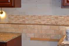 Backsplash install: Use a strip of wood to create a level line on the sheetrock behind the stove.