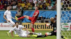 Tim Howard stops the shot of Belgium's Jan Vertonghen, one of numerous saves that kept the U.S. alive through the first 90 minutes of play. Marcio Jose Sanchez / Associated Press