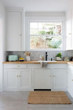 A jute rug accents a gorgeous white and gray kitchen boasting white shaker cabinets fitted with antique brass hardware and a butcher block countertop.