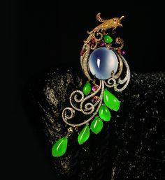 18K金镶翡翠、彩宝及钻石项链/胸针。一款以凤凰为灵感的惊艳之作。运用了玻璃种无色翡翠蛋面、叶形满绿翡翠、水滴形墨翠、粉色蓝宝石与黄白钻,采用立体微钉镶等精湛镶嵌工艺制作而成。