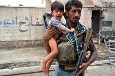Un soldado afgano, con la mirada consternada, salva a un niño que sobrevivió a un ataque terrorista en Afghanistan, 2013.