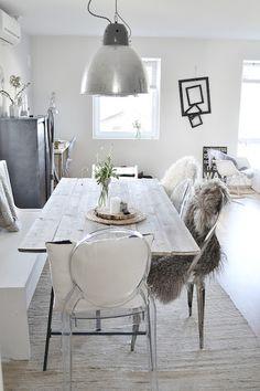 sheepskins, big industrial light, stainless steel furnishings & ghost chair #whitewalls #industrial