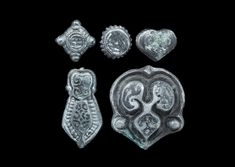 """Viking Niello Belt Mount Group 9th-12th century AD. A mixed group of silver mounts with niello ornamentation, comprising: one teardrop with beaded border; one square with pellet corners; one discoid with pellet border; one heart-shaped; one pelta-shaped with raised scroll detailing. Cf. Sedov, B.B. Finno-Ugri i Balti v Epokhi Srednevekovija, Moscow, 1987, plate XCI, item 36-38. 24 grams total, 12-31mm (1/2 - 1 1/4"""")."""