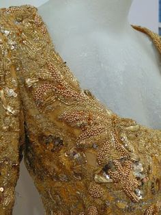Detail of the Dior cocktail dress: extraordinary gold lace heavily embroidered with beads, sequins and metal gold thread.