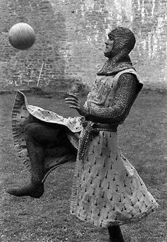 John Cleese playing football in custume during downtime on 'Monty Python and the Holy Grail', 1975