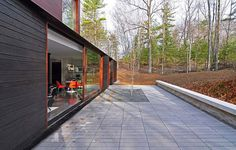 Concrete patio around the beautiful forest house with sliding glass doors - Decoist