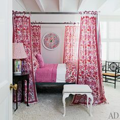 In a bedroom, a Room & Board four-poster is dressed with colorful Roberta Roller Rabbit linens | archdigest.com