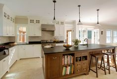 soapstone counters, white cabinets combined with wood pendant lights above island