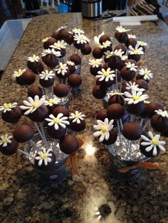 Royal icing daisy decorated chocolate chip cake pops.