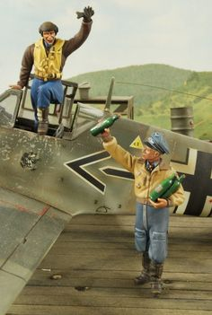 Here we have a pair of WWII Luftwaffe pilots celebrating the ace-qualifying kill. The winning pilot wears officer's breaches, leather flight helmet, and a life preserver vest over his leather jacket. The welcoming pilot wears channel breaches and a privately purchased linnen jerkin popular with the Afrika Korps pilots as he holds a few bottles of wine as he prepares to celebrate the victory.