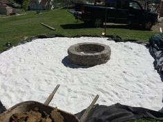 They covered the black tarp with white sand and built a fire pit in the middle of the circle.