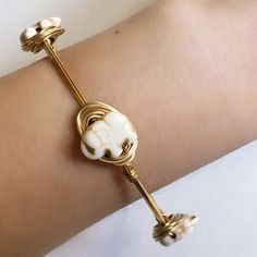 White Elephant Bangle Dainty! Handmade with white howlite elephant stones and gold colored wire. Tarnish resistant. Diameter is 2.75 inches across.  Note: These stones are carved from natural stones. Each one is different and will have natural imperfections and slight color variations. Sydney Elle Jewelry Bracelets
