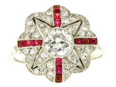 Exquisite Belle Époque ruby and diamond ring in platinum. Old-cut diamond to centre in a rub-over setting has an estimated weight of 0.50cts. With a further forty round eight cut diamonds, grain set to a pierced out scalloped mount, having an approximate total stone weight of 0.40ct. Four lines of calibré-cut rubies, rub-over set with millegrain finish, to a very fine pierced out gallery. Twelve rubies in total weighing approximately 0.36ct. French, circa 1910.
