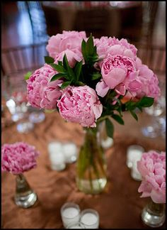 single peony and candles around a center stack of books